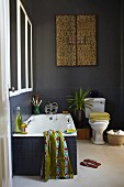 Blick durch offene Tür in dunkelgrau getöntes Bad mit eleganten Farbakzenten, im Hintergrund Kunstobjekt mit Ornamenten an Wand