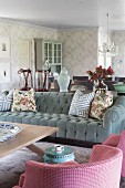 Armchair with pink and white checked cover and grey velvet sofa with scatter cushions around coffee table in romantic, elegant, country-house interior
