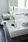 A square console basin on a double washstand with a dark wooden surface with water running from a square wall tap