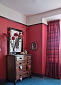 Kommode mit Herzanhängern und Blumenstrauss vor pinkrot getönter Wand, daneben farblich abgestimmter Vorhang in Fensternische