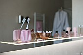 A toothbrush in a pink vintage ceramic cup along with perfume bottles on an illuminated glass shelf
