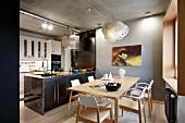 Holzstühle mit weiss lackierter Rückhenlehne um Esstisch vor Küchenblock in offener Küche mit Loft-Charakter