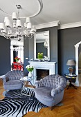 Armchairs with grey velvet upholstery on zebra-skin rug and elegant chandelier in front of mirror above fireplace