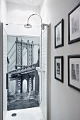 Wallpaper mural with bridge motif as back wall of shower and framed black and white photos on side wall