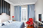 Pale blue blanket on double bed with curved headboard, bedside lamp with red lampshade and balcony door with floor-length curtains