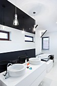 White washstand with twin basins against black and white stripes wall in designer bathroom