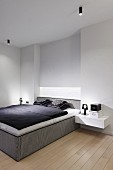 Minimalistisches Schlafzimmer mit Boxspringbett, schwarz-weisse Bettwäsche, seitlich an Wand schwebende Nachttischablage