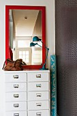 Mirror with red frame and retro table lamp on white chest of drawers