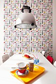 Breakfast crockery on yellow tray on dining table below pendant lamp against wall with wallpapered panel