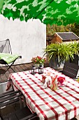 Table with red and white gingham tablecloth and outdoor chairs on terrace
