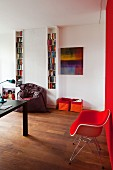 Red, classic armchair against red wall, narrow, white bookcases and fabric storage bins against wall in modern interior