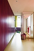 Flat-fronted purple cupboards, colourful waste-paper basket and floor-to-ceiling mirror on wall of modern hallway