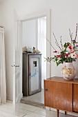 Bauchige Vase mit Blumenstrauss auf Retrokommode, daneben die offene Tür zum Bad Ensuite mit altem Holzschrank