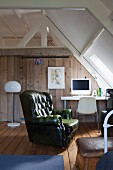 Green leather lounge chair in teenager's attic room; computer on desk against wooden board wall in background