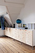 Keyboard and speakers on sideboard with plain wooden doors and fabric loop handles in attic room with jeans hanging from metal rod