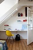 Gelber Klassikerstuhl an Schreibtischeck mit eingebauter Tischplatte und Wandborden unter einer Dachschräge
