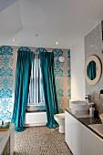 Fenster mit bodenlangem Vorhang in floral gemusterte Tapetenwand, seitlich ein Waschtisch mit Aufsatzbecken auf Unterschränken