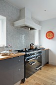 Cooker with extractor hood in modern, fitted kitchen with grey fronts