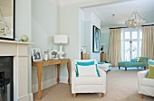 Pale armchair next to artistic console table and chaise longue in elegant living area