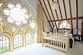 Schlafbereich mit Dachschräge und Kinderbett vor Doppelbett in umgebauter Kirche, prunkvolles Fenster, teilweise in Rosettenform mit Buntglaselementen