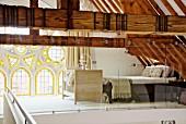 Blick in Schlafbereich auf Galerie, hinter Glastrennwand, alte Holzkonstruktion und neogotisches Fenster mit Rosetten und Buntglaselementen