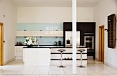 Free-standing counter with shelves and designer bar stools on white tiled floor in open-plan, modern fitted kitchen