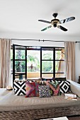 Ceiling fan above couch with geometric scatter cushions in front of open terrace doors