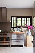Modern stainless steel kitchen counter, stone floor and Delft vase of Bougainvillea below lattice windows