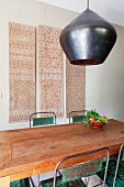 Hand-crafted pendant lamp above dining table and battered metal chairs in front of ethnic wall-hanging