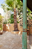 Wooden column with distressed green paint on Mediterranean terrace with palm trees