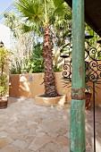 Grün patinierte, kunsthandwerklich verzierte Holzstütze auf mediterraner Terrasse mit Palmen