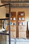 Bücher und Kunstobjekt auf Holzständern auf überdachter Terrasse