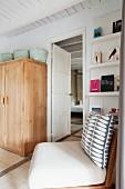 Stuhl mit gemustertem Kissen vor Bücherregal und einfacher Holzschrank in mediterranem Schlafzimmer