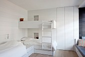 Zwei übereck gestellte Betten und ein Hochbett im weissen Kinderzimmer