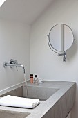 Concrete washstand with water running out of wall-mounted taps and swivelling vanity mirror