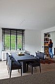 Long table and chairs in slate grey in modern interior; woman in background in front of bookcase with stacked firewood