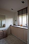 Viel Stauraum im eingebauten Waschtisch vor Fenster mit halb geöffneter Jalousie