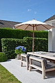 Large parasol and blue hydrangea in planter in front of clipped hedge; dining area with wooden furniture and grey seat cushions