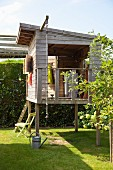 Wooden playhouse on stilts with climbing rope in garden of holiday home