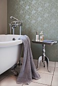 Vintage, clawfoot bathtub next to postmodern, silver-coated side table against wall with rolled paint pattern