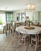 Pendant lamp above dining area with round, white table and Thonet chairs painted pale grey; lounge area in background in bright, modern interior