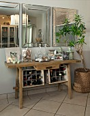 Rustic console table with small wine rack below three bevelled mirrors