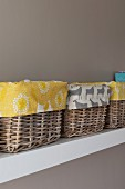 Detail of several baskets lined with patterned fabrics on white shelf on pale grey wall