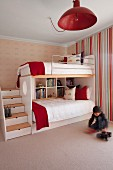 Little boy sitting on floor below pendant lamp with red metal lampshade and bunk beds with stairs in children's bedroom