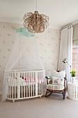 Ovales Gitterbett mit Baldachin neben Schaukelstuhl an Fenster, Deckenleuchte mit Schirm aus gebogenen Holzsteifen
