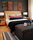 Double bed with wooden headboard and bolster in red, white and black stripes; old road signs on wall painted dark gray and laptop on ottoman