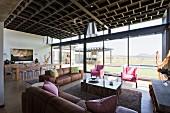 Offener Wohnraum mit Loungebereich vor verglaster Fassade mit Landschaftsblick, kassettenartige Decke in zeitgenössischem Wohnhaus