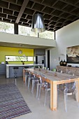 Rustic, solid wood table and Ghost chairs; open-plan kitchen with yellow wall in background and coffered-style ceiling