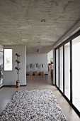 Rug in natural shades in hallway with exposed concrete ceiling, glass wall and plants on tree stump stools in background