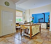 Free-standing counter, modern barstools and AGA cooker in blue-painted niche in open-plan kitchen